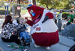 Reno Aces mascot Archie high fives 4-year-old Aidan Phillips with help from babysitter Aurora Guerro during the grand opening of Inspiration Station, located at Dick Taylor Park in Reno.  The Junior League of Reno and the City of Reno celebrated the opening of the regions only universally accessible playground on Saturday afternoon, October 20, 2012.