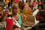 An African American teenage girl lights a Kwanzaa candle for Ujima (Collective Work and Responsibility) at a Community Kwanzaa Celebration, Long Beach, CA