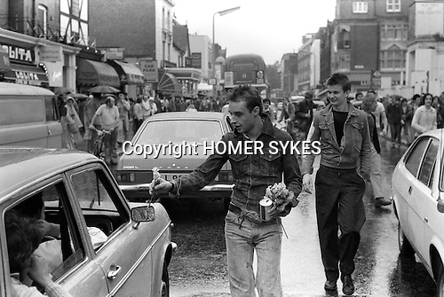 Punk Mick Bladder, hand out flowers to passing car drivers stuck in traffic. Kings Road, Chelsea, London. England. 1977.