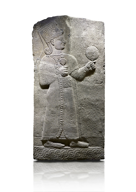Hittite relief sculpted orthostat stone panel of Long Wall Basalt, Karkamıs, (Kargamıs), Carchemish (Karkemish), 900-700 B.C. Anatolian Civilizations Museum, Ankara, Turkey.<br /> <br /> Goddess Kubaba. Goddess is depicted from the profile. The part below the chest of the relief is broken. She holds a pomegranate in her hands on her chest. She carries a one-horned headdress on her head. Her braided hair hangs down to her shoulder. The text in the hieroglyphics is not understood. The lower part of the relief has been restored. <br /> <br /> On a White Background.