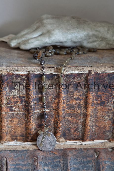 Detail of a necklace hanging over the corroding leather binding of a stack of antique books