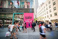 Shoppers pass the TopShop store, offering a 50% discount, on Fifth Avenue in New York on Friday, June 30, 2017.  (© Richard B. Levine)