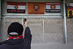 A fan taking a picture of flags inside Broadhurst Park, Manchester, the new home of FC United of Manchester before the club's match against Benfica, champions of Portugal, which marked the official opening of their new stadium. FC United Manchester were formed in 2005 by fans disillusioned by the takeover of Manchester United by the Glazer family from America. The club gained several promotions and played in National League North in the 2015-16 season, but lost this match 1-0.