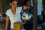 A village woman in Costa Rica pours hot water from a kettle to make coffee.
