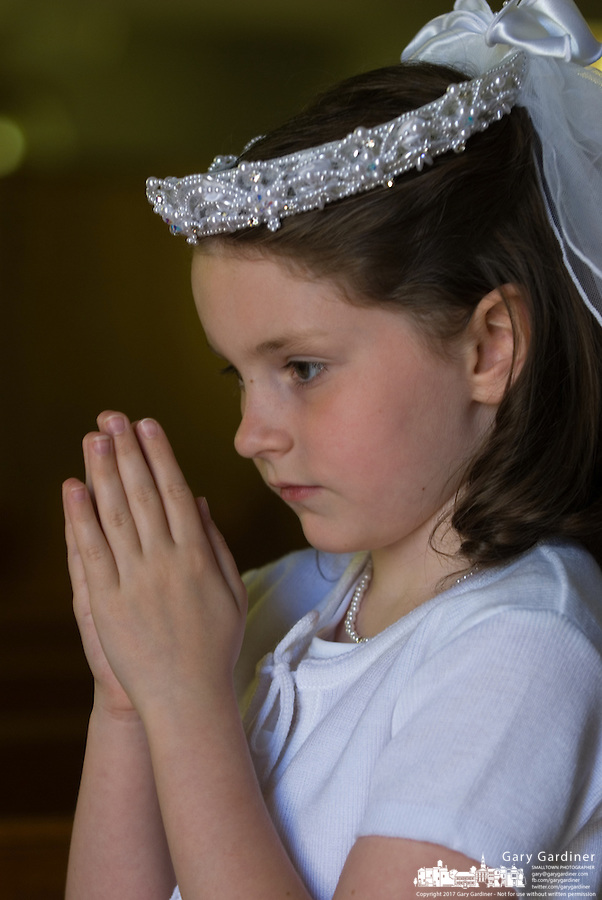 A young girl stands with her hands raised in prayer after her first communion sacrament at a Catholic church in Johnstown, OH.<br />