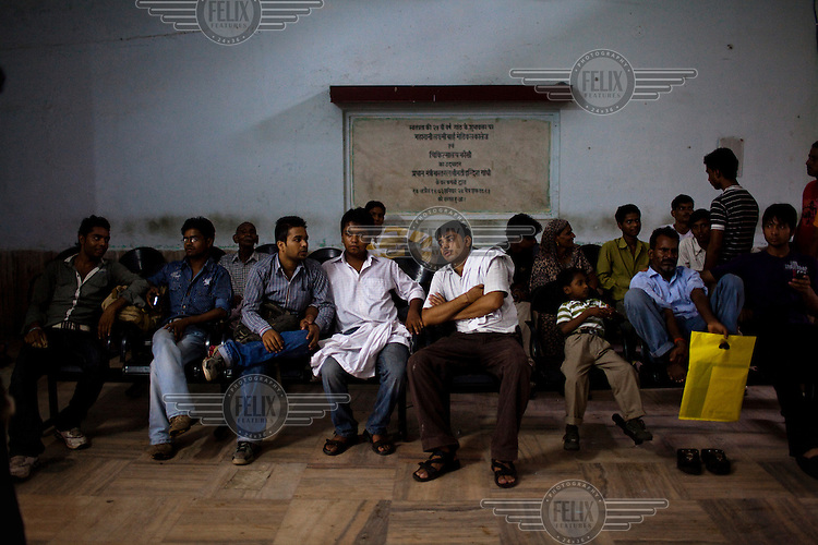 People wait in a waiting room to see a doctor at the Maharani Laxmibai Medical College.