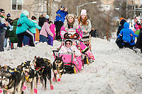 DeeDee Jonrowe runs down Cordova Street giving high-fives to spectators during the Ceremonial Start of the 2016 Iditarod in Anchorage, Alaska.  March 05, 2016