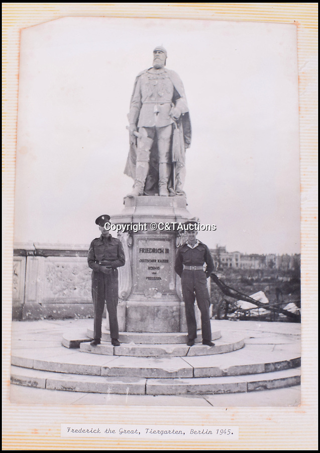 BNPS.co.uk (01202 558833)Pic: C&TAuctions/BNPS<br /> <br /> Guardsman pose next to a statue of Frederick the Great in the devastated Tiergarten.<br /> <br /> Reich in Ruins - An incredible album of unseen photographs from Hitler's devastated Reich Chancellery, taken one of the first British soldiers into a devastated Berlin has come to light.<br /> <br /> The photo album was compiled by an elite soldier of the 1st Battalion Grenadier Guards that rolled into Berlin on 4th of July 1945. <br /> <br /> The photos show the inside of Hitler's spacious private office from behind his imposing desk and the conference hall where the Nazi high command met to plot their next move.<br /> <br /> By the time the unknown Guardsman set foot in the chancellery, its lavish marble interior had been battered by the Red Army assault and only a pile of rubble remained.<br /> <br /> The soldier composed an album of his own photographs alongside Nazi publicity postcards from the heyday of the Third Reich.