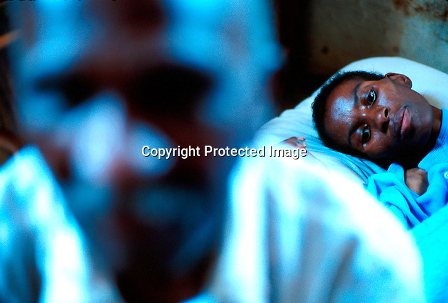 disiaids00273  Social Issues, Aids, Health. A woman dying of Aids in the family house in Murchison, Southern Natal in South Africa. The father sits next her bed. She died a few days later..©Per-Anders Pettersson/iAfrika Photos