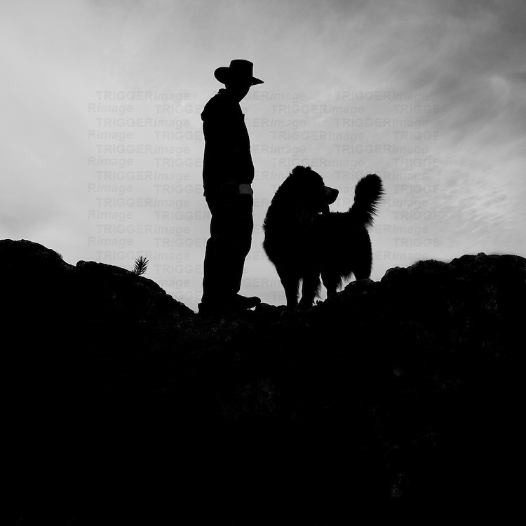 A silhouetted man and his dog standing on a ridge