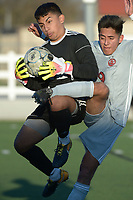 NWA Democrat-Gazette/ANDY SHUPE<br /> Springdale senior Michael Martinez (right) and Rogers junior goal keeper Anthony Garcia collide Tuesday, April 10, 2018, as Garcia secures the ball during the second half at Jarrell Williams Bulldog Stadium in Springdale. Visit nwadg.com/photos to see more photographs from the match.