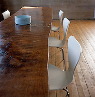 The organic shape of this handcrafted table contrasts with the precision of the Arne Jacobsen moulded plywood chairs in this dining room created in a converted church