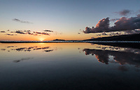 Tidal pools near Koko Head in Hawai'i Kai reflect a golden sunset over O'ahu; a distant Diamond Head is on the left.