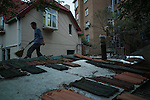 A man cleans the roof of his house in the old town of Qingdao.