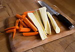 Chopped sliced carrots and parsnips on wooden chopping board in kitchen