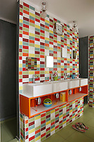 The boys have their own basin in the large family bathroom where the tiles have been chosen to match their bedroom doors and the mirrors are placed according to the height of each child