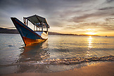 INDONESIA, Flores, Riung, a boat floats in the Flores Sea at sunset on Rutong island