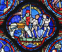 A knight waits for his horse to finish grazing so he can go to war and 2 naked male twins hold hands and dance (these are traditionally Castor and Pollux, sons of Jupiter), section of May and Gemini, from the Zodiac and the labours of the months stained glass window, 1217, in the ambulatory of Chartres Cathedral, Eure-et-Loir, France. This calendar window contains scenes showing the zodiacal symbol with its corresponding monthly activity. Chartres cathedral was built 1194-1250 and is a fine example of Gothic architecture. Most of its windows date from 1205-40 although a few earlier 12th century examples are also intact. It was declared a UNESCO World Heritage Site in 1979. Picture by Manuel Cohen
