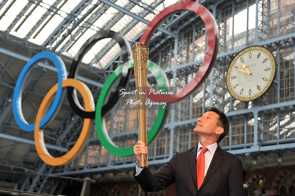 Sebastian Coe (Chairman of LOCOG) looks up at the torch as he holds it under the Olympic rings. 2012 London Olympic Torch Prototype designed by Edward Barber and Jay Osgerby. St Pancras Station. London. 08/06/2011. MANDATORY Credit Sportinpictures/Garry Bowden - NO UNAUTHORISED USE - 07837 394578