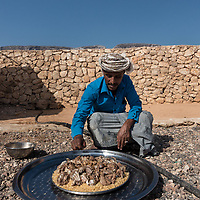 Dec. 25, 2014 - Socotra, Yemen. Saad brings food to guests in his home in Neet. A traditional festive meal will start with a glass of warm broth,with the bones of a goat, the main meal is goat meat and rice, for desert a cup of red tea. © Nicolas Axelrod / Ruom