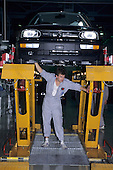 Bratislava, Slovakia. Production line worker underneath a car on a lift; Volkswagen factory.