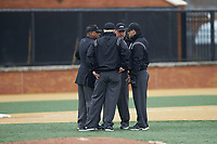 The umpiring crew get together to discuss a call during the ACC baseball game between the Notre Dame Fighting Irish and the Wake Forest Demon Deacons at David F. Couch Ballpark on March 10, 2019 in  Winston-Salem, North Carolina. The Demon Deacons defeated the Fighting Irish 7-4 in game one of a double-header.  (Brian Westerholt/Four Seam Images)