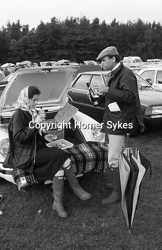 Picnic at polo match Windsor Great Park, the car park. Berkshire England. Circa 1985. Wealthy upper class style, the woman is wearing a Hermes headscarf and blue Burberry waxed jacket as is he plus a flat tweed cap. Shes on Bucks Fizz he's drinking Champagne.