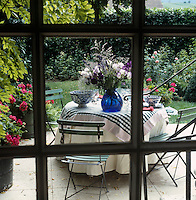 A view through the window to the patio on which stands a table covered in green and white table linen