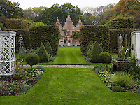 Flowerbeds are arranged symmetrically with a simple fountain one side and a free-standing trellis on the other