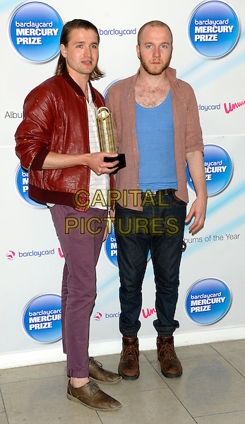 WILD BEASTS - Hayden Thorpe & Tom Fleming .attend photocall to announce the nominations for The Barclaycard Mercury Prize, The Hospital, Endell St, London, England, UK, July 20th 2010..music full length award trophy red leather jacket blue t-shirt purple trousers brown boots shoes .CAP/CJ.©Chris Joseph/Capital Pictures.