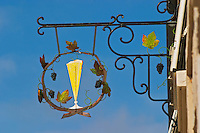 A wrought iron painted sign that illustrates the theme of champagne and wine production: a glass of champagne and a vine with grapes, the village of Hautvillers in Vallee de la Marne, Champagne, Marne, Ardennes, France