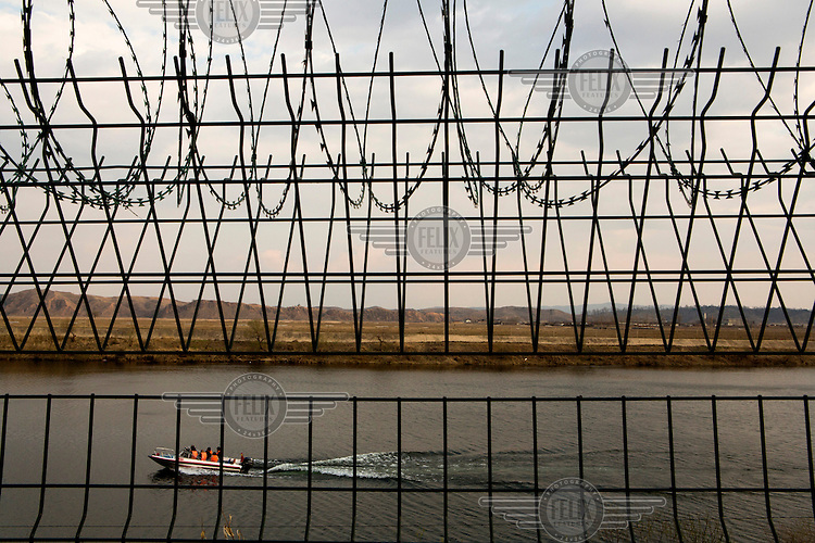 Razor wire obscures a boat carrying Chinese tourists on a pleasure ride along the Yalu River which also forms the border between North Korea and China. /Felix Features