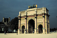 Arc de Triomphe du Carrousel crisp in bright nearly frontal morning light. Background buildings and trees in shadow under blue-grey sky. People. Paris, France.