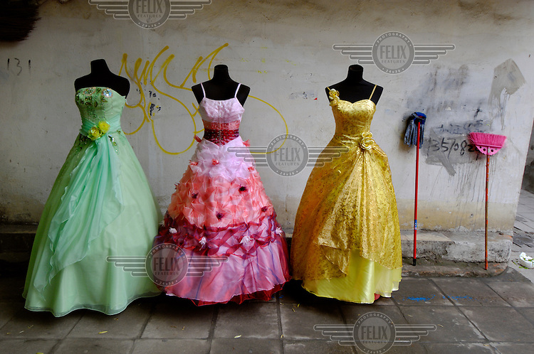 Mops and colourful wedding dresses for sale in a side alley off the wedding dress market, feeding a new trend of brides who are buying their dresses rather than hiring them. These particular dresses are for sale at a little over 20 USD each.