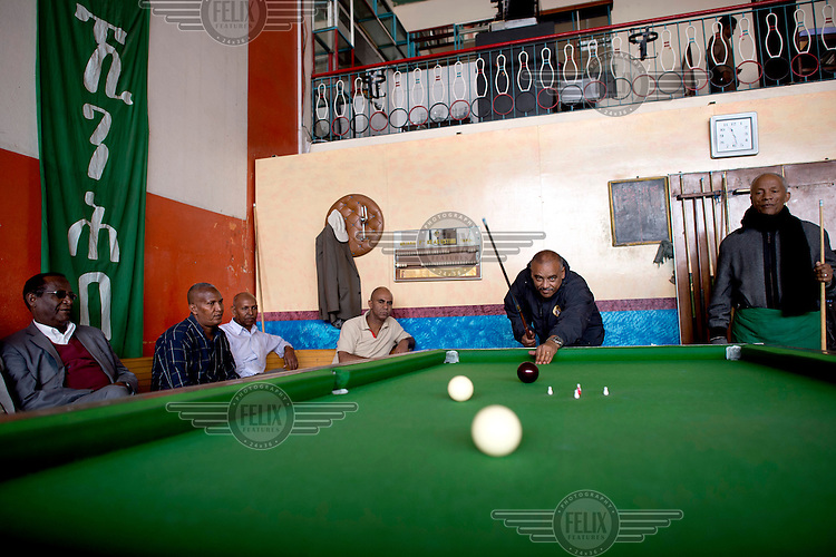 Elderly men playing billards inside the Multi Sport Club. They play a form of five-pin billiards, originally an Italian billiards game.
