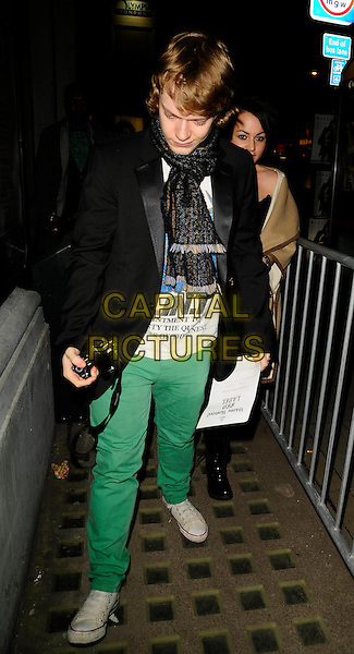 ALFIE ALLEN & JAIME WNSTONE .At the Vivienne Westwood Autumn Winter Fashion Show during London Fashion Week, National hall, Olympia, London, England, February 21st 2009..full length black jacket scarf Jamie green  jeans trousers girlfriend boyfriend couple camera converse trainers white .CAP/CAN.©Can Nguyen/Capital Pictures