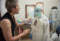 "Occidental College professor Mary Beth Heffernan applies an adhesive portrait to Zoe Dewalt, RN before Dewalt enters the ""red zone"" to care for unconfirmed Ebola patients in the ELWA II ETU (Ebola treatment unit), Monrovia, Liberia on March 12, 2015. Heffernan's PPE Portrait Project involves creating wearable portraits of the health care workers who must wear PPE (personal protective equipment) when working with patients.<br /> (Photo by Marc Campos, Occidental College Photographer) Mary Beth Heffernan, professor of art and art history at Occidental College, works in Monrovia the capital of Liberia, Africa in 2015. Professor Heffernan was there to work on her PPE (personal protective equipment) Portrait Project, which helps health care workers and patients fighting the Ebola virus disease in West Africa.<br />