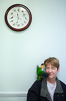 "Jonda Vance squints as ""Harley,"" her black-headed Caique parrot, flaps in her face in the exam room of the Avian Health Clinic in Reynoldsburg, Ohio, on Oct. 27, 2012."
