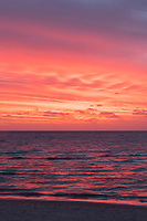 The sun sets in a blast of pink which reflects off the ocean at Brighton Beach, Adelaide, Australia.