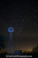 The windmill is spinning in this image as you can see the stars in the sky behind in the Texas Hill Country.