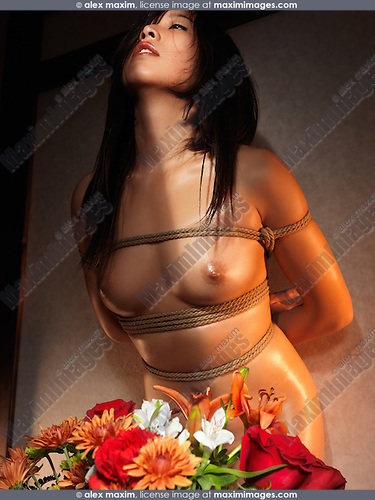 Artistic nude photo of Flowers in front of a Beautiful naked Japanese woman tied with Shibari rope bondage