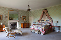 A wide variety of patterns have been used in this bedroom; from silver wreathes on the wallpaper, floral sprigs on the bed hangings, to a bold, multi-coloured, quilted bed cover