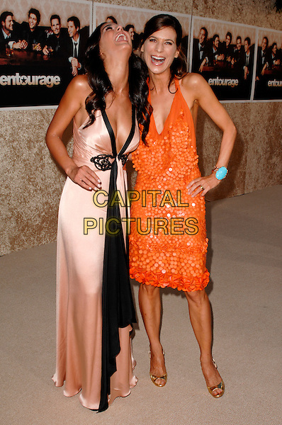 "EMMANUELLE CHRIQUI & PERREY REEVES.The Los Angeles Premiere of the HBO Original Series ""Entourage"", 6th Season held at Paramount Studios in Hollywood, California, USA. .July 9th, 2009 .full length pink cream silk satin black trim plunging dress orange halterneck  hand on hip cleavage looking up mouth open laughing.CAP/ROT.©Lee Roth/Roth Stock/Capital Pictures"