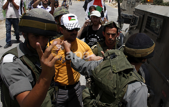 Israeli soldiers arrest a Palestinian protester after he burnt the Israeli flag during a demonstration by Palestinian, Israeli and foreign peace activists against Israel's controversial separation barrier in the West Bank village of Maasarah, near the biblical town of Bethlehem, on June 11, 2010. Photo by Mamoun Wazwaz