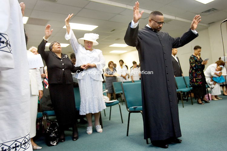 WATERBURY CT. 21 September 2013-092113SV04-At right, The Rev. T. Charles Brantley of Restoration Springs Interdenominational Church prays during an ordination service at the church in Waterbury Saturday. Brantley was named a bishop at the service. <br /> Steven Valenti Republican-American