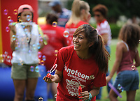 NWA Democrat-Gazette/ANDY SHUPE<br /> Daisy Mota, an incoming freshman at the University of Arkansas from Dallas, laughs Saturday, June 17, 2017, while blowing soap bubbles during the Juneteenth celebration in The Gardens on the University of Arkansas campus in Fayetteville. Juneteenth marks the anniversary of the emancipation of slaves in the United States.
