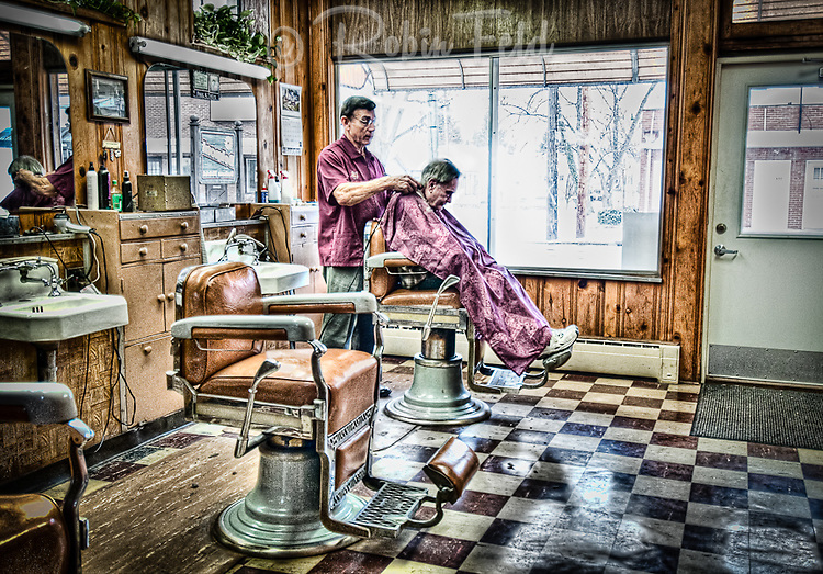 Barber cutting hair in small barbershop. Small business and Americana series.
