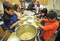 NWA Media/Michael Woods --12/14/2014-- w @NWAMICHAELW...Temple Shalom religious school students (left to right) Eli Dranow, Joa Murray, Lily Adler and Luu Adler help make latkes (a potato pancake) for their annual Hanukkah party Sunday afternoon in Fayetteville.  Hanukkah officially begins on Tuesday at sundown.