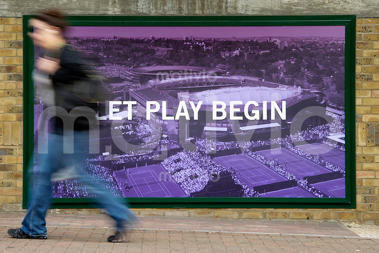A person walks in front of an advertising poster of the Wimbledon shop Preparation for The Wimbledon Championships 2010 The All England Lawn Tennis & Croquet Club  Saturday Pre Championships Saturday 18/06/2010