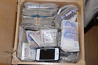 Pictured: Cash found as evidence<br /> Re: A drugs gang has been jailed for a total of sixty-two-and-a-half years after South Wales Police disrupted a drugs run from London to Cardiff and uncovered a sophisticated and lucrative criminal operation.<br /> Seven men were sentenced today after they were each convicted of being involved in the supply of Class A and B drugs at previous hearings at Cardiff Crown Court.<br /> The jury heard officers from the force&rsquo;s Organised Crime Unit confronted driver Stuart Jarman at Membury Services on the M4 on March 15th this year &ndash; and discovered 2kg of cocaine. Analysis of the Class A drug found it was 80% pure with a street value of &pound;450,000.<br /> Jarman&rsquo;s arrest led officers to six other gang members &ndash; as well as a large-scale cannabis factory in Ammanford and another in Waunarlwyd, as well as an illegally-held live handgun.<br /> The following are today starting lengthy sentences after being convicted of conspiracy to supply Class A drugs:<br /> Stuart Jarman, 41, of Garden City, Rhymney, jailed for 6 years;<br /> Lec Gjoka, 42, of Greenwich, London, jailed for 14 years;<br /> Jason Theobald, 42, of Hill Street, Rhymney, jailed for 10 years;<br /> Lyndon Evans, 37, of Wind Street, Ammanford, jailed for nine years;<br /> John Knight, 36, of Pleasant Street, Pentre, jailed for 18 years.<br /> Evans and Knight had also admitted a separate charge of conspiring to supply cannabis, alongside Anthony Vobe, 41, of Garnant, Ammanford, who was jailed for three years for conspiracy to supply cannabis.<br /> A seventh defendant, Richard Phillips, 51, of Barnabas Close, Waunarlwydd, Swansea, was jailed for two-and-a-half years after he pleaded guilty to possessing a firearm whilst banned from doing so due to previous convictions, and conspiracy to produce cannabis. It was at his farm that officers located the firearm and one cannabis factory.<br /> The second cannabis factory was located in Ammanford and &ndash; at the time of being raided &ndash; had the potential to net the gang a further estimated &pound;70,000.<br /> Actin